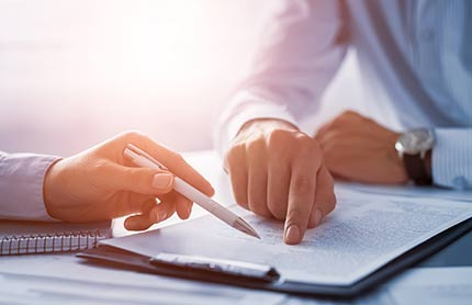Closeup of contract on a desk being examined by two people