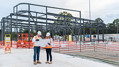 A man and a woman wearing hard hats and high vis looking at plans at a building site