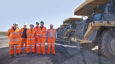 Miners in hard hats and high visibility vests standing near large mining vehicle tyre