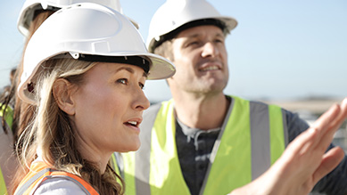 A woman pointing to something outside of the fram with a man and one other person all wearing hard hats and high vis vests